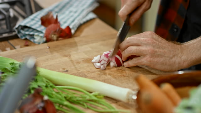 LD Hands of male chef cutting a red onion on a wooden board in the kitchen video