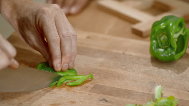 Hands of male chef cutting green pepper on a wooden cutting board
