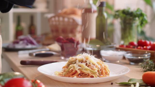 vidéos et rushes de mains de fromage de grille de cuisson mâle au-dessus des pâtes cuites - parmesan