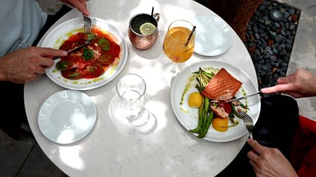 stockvideo's en b-roll-footage met handen van man en vrouw eten maaltijd aan tafel - restaurant table