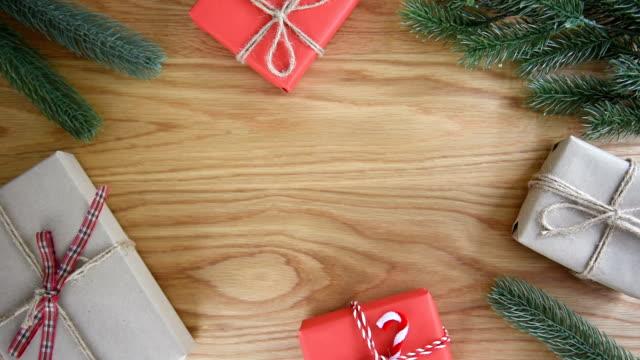 vidéos et rushes de mains d'homme, plaçant une boîte présente sur fond en bois avec décoration cadeau. - emballé