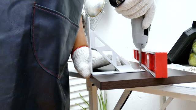 電気 srewdriver を使用してメカニックの人の手のスピン強化木製の棚で、アセンブリ ホーム diy の腕をねじ - 兵卒点の映像素材/bロール