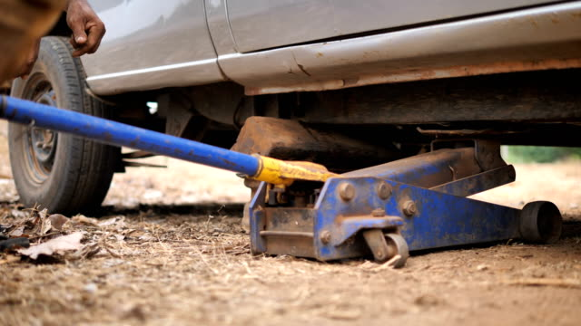 hands of mechanic using car jack to lift up the truck to repair wishbone control arm and replace the front wheel of the car - leva video stock e b–roll