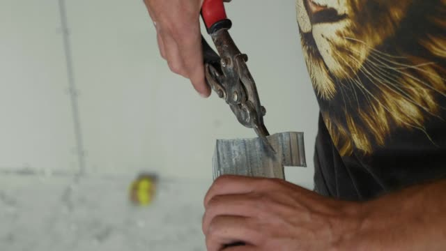 Hands of men cutting frame for mount drywall in unfinished apartments video