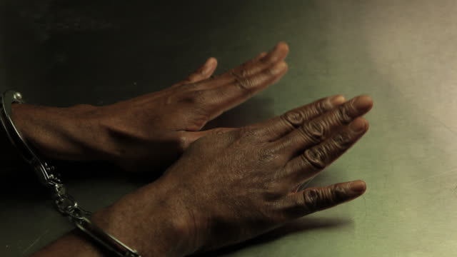 Hands of old black man with handcuffs waiting to be released.  Manos de hombre viejo de raza negra con esposas esperando que lo liberen video