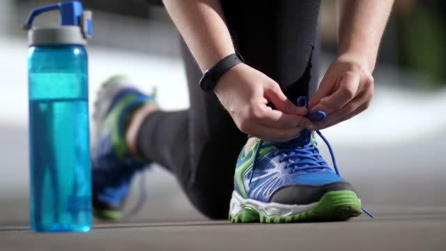 Hands of plus size woman runner tying shoelaces