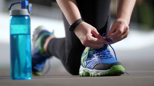 mani di plus size donna corridore legare lacci delle scarpe - annodare video stock e b–roll