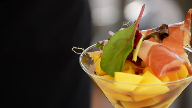 Hands of professional chef decorating cup mango fruit and ham with herbs detail video