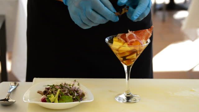 Hands of professional chef decorating cup mango fruit and ham with herbs video