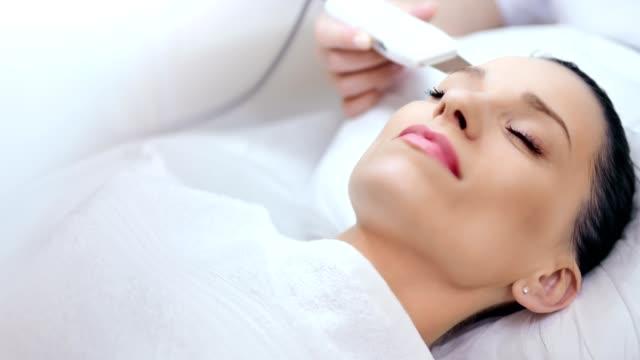 hands of professional female cosmetologist making anti acne and anti-aging face procedure - kosmetyczka praca w salonie piękności filmów i materiałów b-roll
