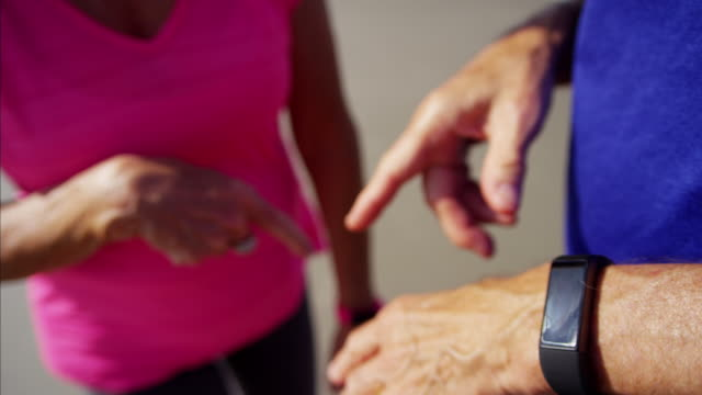 Hands of retired Caucasian couple using wearable technology video