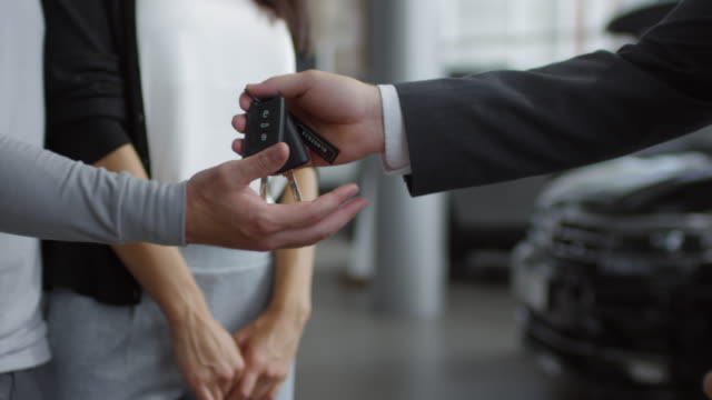 Hands of Salesman Giving Car Key to Family Couple in Auto Showroom Close up shot of hands of salesman giving car key to man standing with wife in auto showroom car shopping stock videos & royalty-free footage