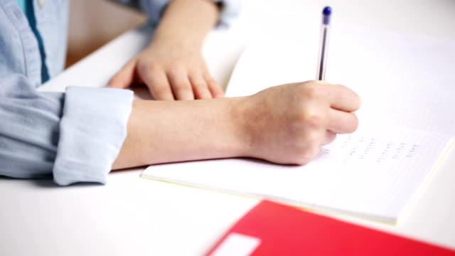 eller öğrenci kız okulda not defterine yazma - çalışma kitabı stok videoları ve detay görüntü çekimi