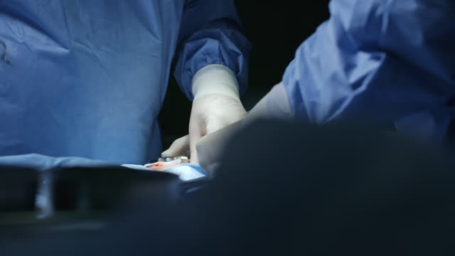 Hands of Surgeon Operating on Patient PAN with close up of hands of skillful surgeon in scrubs and gloves operating on patient under anesthesia operating stock videos & royalty-free footage
