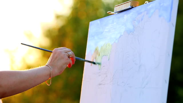 hands of the artist with a brush, paint a picture on an easel in the open air - tavolozza video stock e b–roll