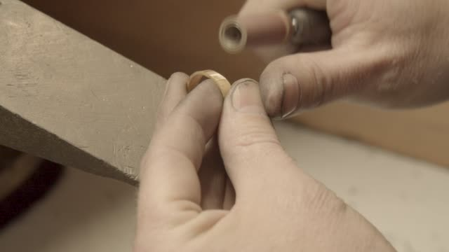 Hands of the jeweler polishes ring with the polishing machine video
