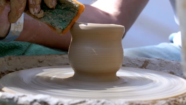 Hands of the Master Potter and Vase of Clay on the Potter's Wheel