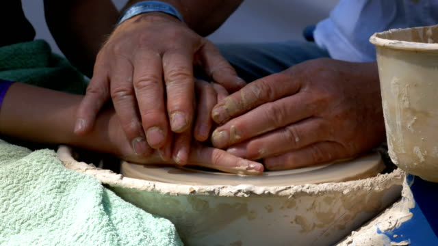 Hands of the master potter and vase of clay on the potter's wheel close-up
