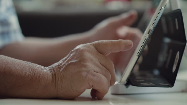 Mains de la vieille femme et la tablette électronique. - Vidéo
