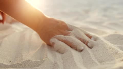 vídeos de stock e filmes b-roll de hands of unknown young girl touching white sand - areia