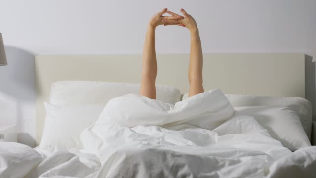 hands of woman awaking in bed at home - vídeo