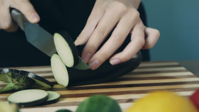 Hands of woman cutting eggplant on wooden board. Close up. Ring of eggplant. Cut vegetables for salad. Healthy food.