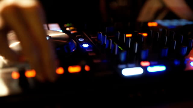 Hands of woman DJ tweak various track controls on dj's deck at night club video