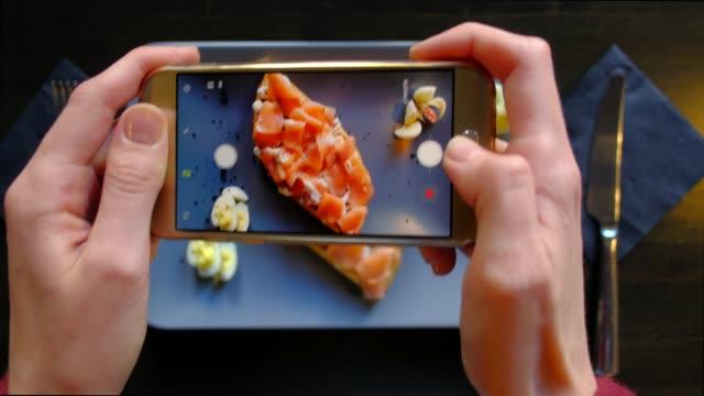 vídeos y material grabado en eventos de stock de manos de mujer fotografiando apetitoso comida por teléfono inteligente en el restaurante. 4k. deliciosos gofres frescos con pescados rojos listos en la cafetería. - gastronomía fina
