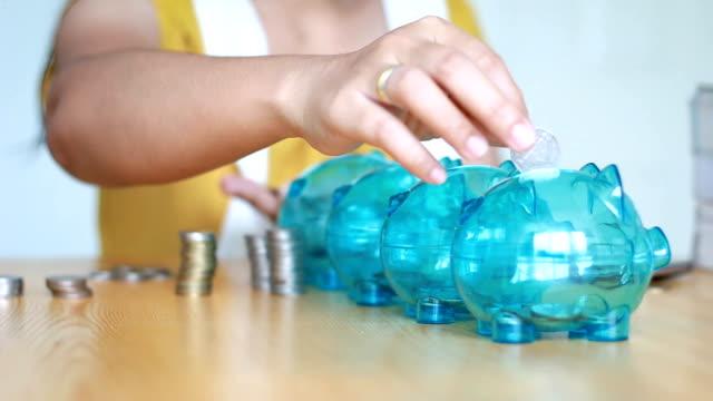 händer kvinna att sätta pengar mynt i 4 klar spargris med tom metafor separat typ av pengar för att spendera och spara i skillnad budget ekonomiskt koncept - dept bildbanksvideor och videomaterial från bakom kulisserna