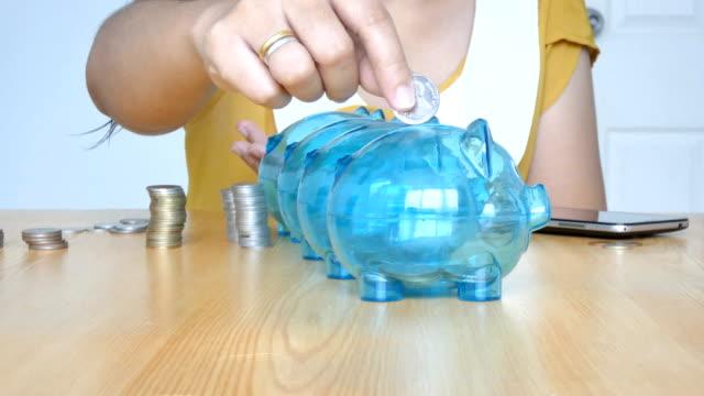 händerna på kvinnan sätta pengar mynt i 4 tydliga spargris med tom metafor separat typ av pengar för utgifter och spara i skillnaden budget finansiella begrepp - dept bildbanksvideor och videomaterial från bakom kulisserna