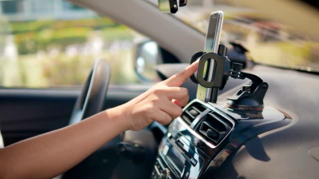 vídeos y material grabado en eventos de stock de manos de mujer con smartphone en un coche de concepto de futurista y tecnología de aplicación de transporte - dirección