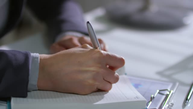 hands of woman writing with pen - promemoria video stock e b–roll