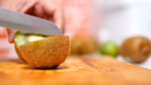 vídeos de stock e filmes b-roll de hands of women using a knife sliced the kiwi fruit into pieces on wooden board in a kitchen - kiwi