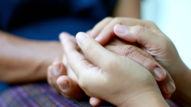 Hands of young woman holding and gentle touch to Hands of old women metaphor and concept for body language feeling love soothe and hope of family old mother and young daughter video