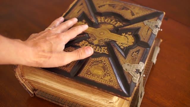 stockvideo's en b-roll-footage met handen op antieke bijbel - heilig geschrift