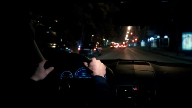 Hands on the wheel. The driver driving a black car at night. video