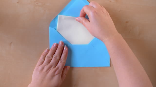SLO MO LD Hands opening a blue envelope and taking out a sheet of paper
