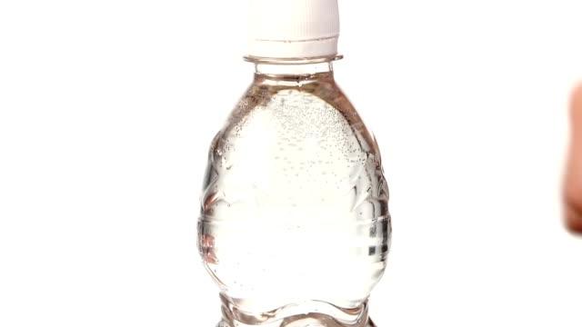 händer öppna en flaska av färskvatten på vit, slowmotion, cam rör sig uppåt - pet bottles bildbanksvideor och videomaterial från bakom kulisserna