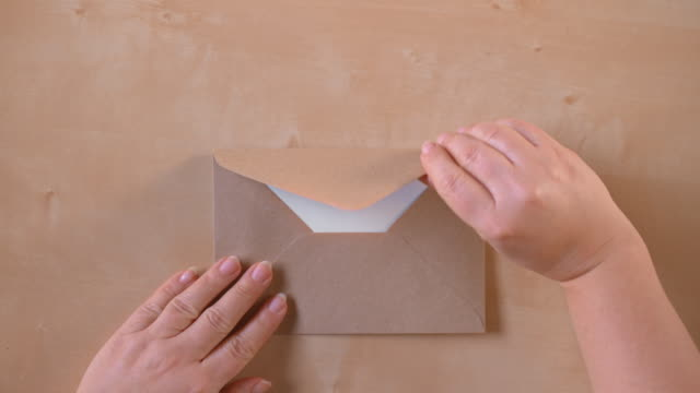 SLO MO LD Hands opening a brown envelope and taking out a sheet of paper