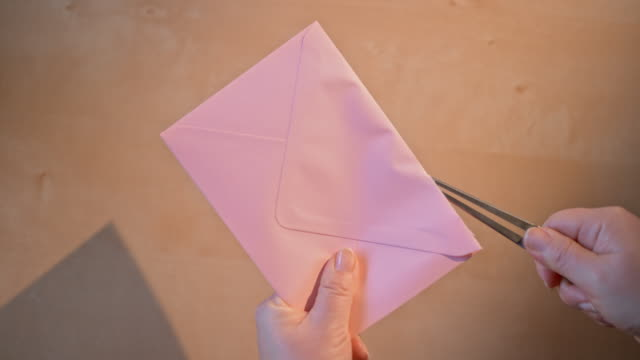 SLO MO LD Hands opening a pink envelope with a knife