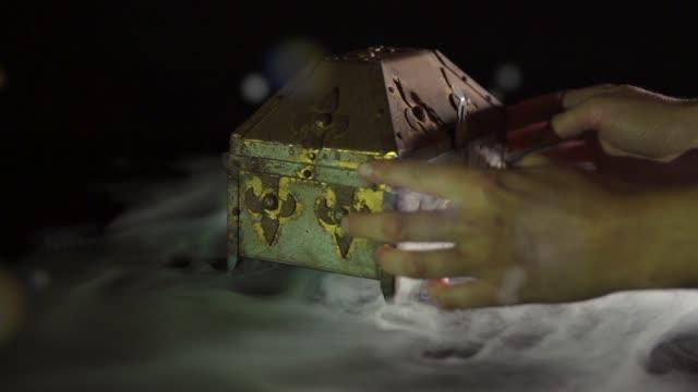 hands opening treasure chest / pandoras box fog smoke on black background video