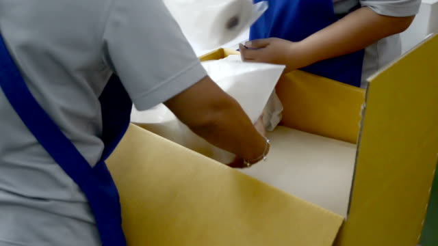 Hands packing goods into box video
