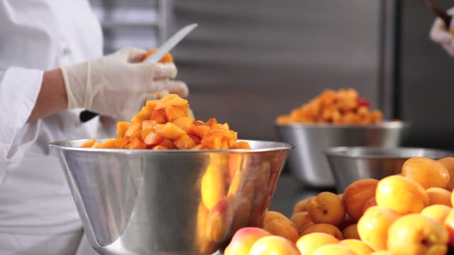 hands pastry chef cutting apricots, prepare the jam in industrial kitchen worktop - albicocca video stock e b–roll