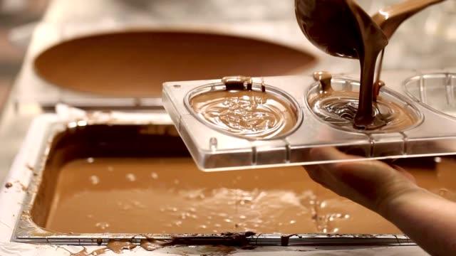 mani chef pasticciere lavoro uova di pasqua al cioccolato - modella negozio video stock e b–roll