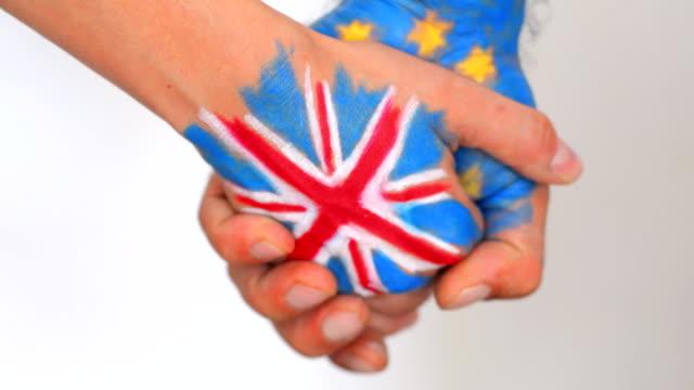 händer mönstrad med flaggor av storbritannien och eu bryter mot unionens - brexit bildbanksvideor och videomaterial från bakom kulisserna