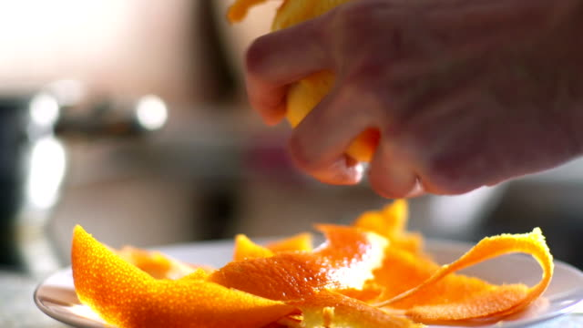 hands peel rind from orange video