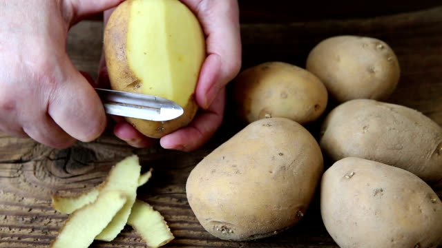 hands peeling potato on rustic wooden table - patate video stock e b–roll