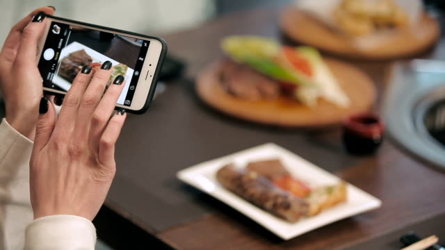 Hands photographing food by smartphone video
