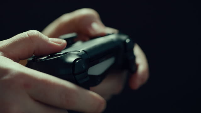 hands play a video game game controller in. extreme close up with shallow depth of field. - telecomando background video stock e b–roll