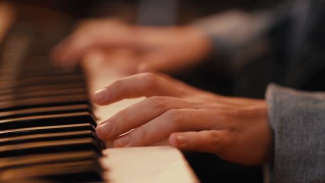 vídeos de stock, filmes e b-roll de mãos tocam música no piano. um pianista executa uma melodia em um sintetizador. - música acústica